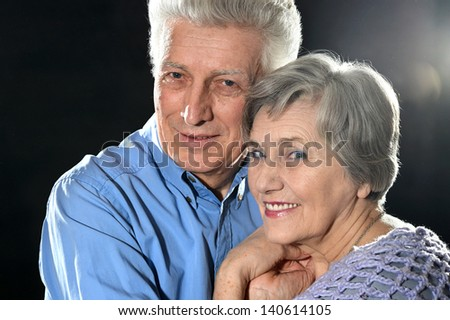 Portrait of older couple embracing on a black background