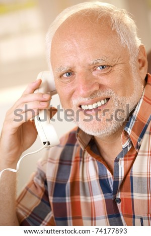 Portrait of older man on landline phone call, smiling happily at camera.?