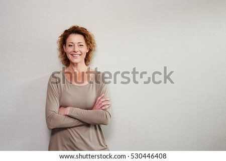 Portrait of older woman smiling with arms crossed by wall #530446408