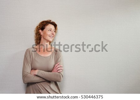 Shutterstock Portrait of older woman standing with arms crossed looking away smiling