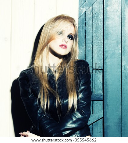 Stock Photo Portrait of one attractive sensual sexy young serious passionate blonde woman with long hair in leather black jacket in studio on wooden wall background, square picture
