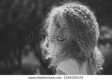Portrait of one beautiful sensual charming blonde young smiling woman with long curly hair and sweet joyful face looking forward sunny day outdoor on natural background, horizontal picture