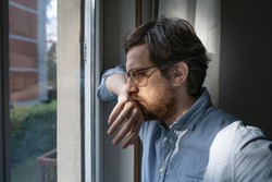 Portrait of one guy longing and looking through window