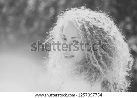 Portrait of one pretty pensive cute blonde young smiling woman with long curly hair and sweet joyful face looking away sunny day outdoor on natural background, horizontal picture