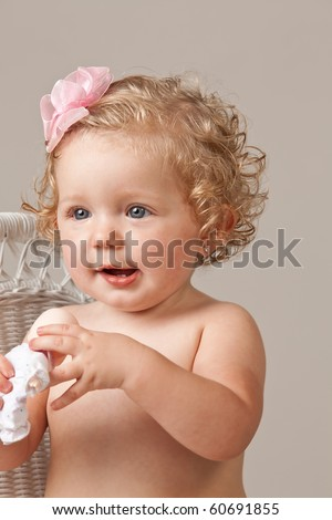 Portrait of one year old baby girl wearing pink bow in hair holding a toy doll.