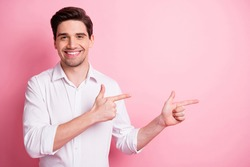 Portrait of optimistic funny guy point empty space wear white shirt isolated on pink color background
