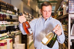 Portrait of ordinary man buying wine in supermarket