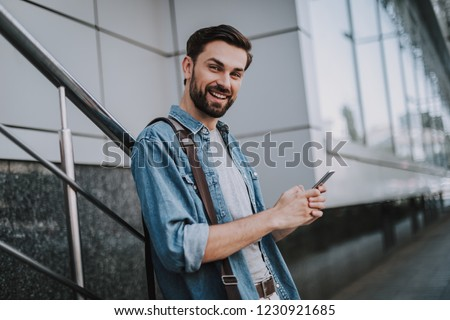 Portrait of outgoing bearded male typing in mobile while looking at camera outdoor