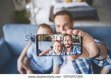 Portrait of outgoing parent and glad child doing photo by mobile