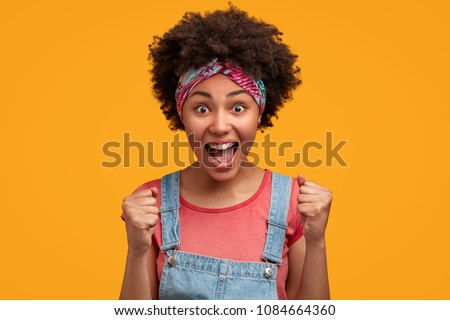 Portrait of overjoyed female clenches fists with happiness, opens mouth widely as shouts loudly, celebrates her success, poses against yellow background. Happy African woman with joyful expression #1084664360