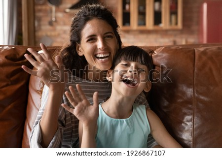 Portrait of overjoyed Hispanic young mom and little daughter wave greet at camera talk on video call at home. Smiling Latino mother and small 8s girl child have webcam digital virtual online event.