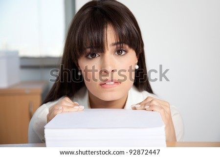 Portrait of overstrained woman at her desk with pile of paperwork