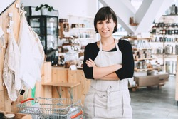 Portrait of owner of sustainable small local business. Female seller assistant of zero waste shop on interior background of shop. Smiling young woman in apron standing in plastic free grocery store.