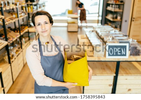 Portrait of owner of sustainable small local business. Shopkeeper of zero waste shop standing on interior background of shop.Young woman in apron holds paper bag of plastic free store. Photo stock ©