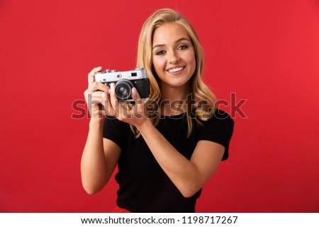 Portrait of paparazzi woman 20s holding and taking photo on retro camera isolated over red background in studio