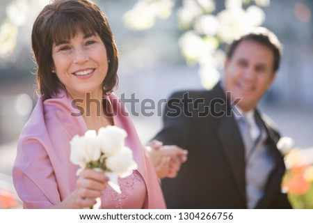 Portrait of parents at wedding with woman holding roses