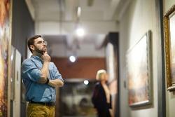 Portrait of pensive bearded man looking at paintings standing in art gallery or museum, copy space