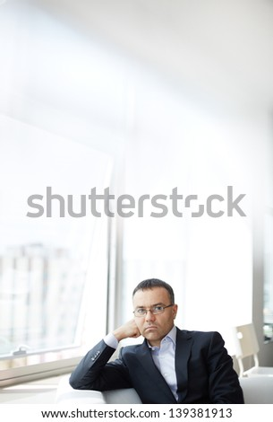 Portrait of pensive businessman sitting in office
