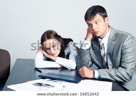 Portrait of pensive businesswoman and businessman sitting at the table with documents on it