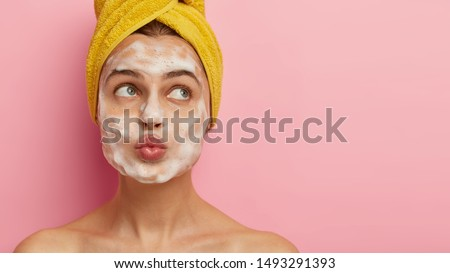 Portrait of pensive European lady keeps lips folded, looks aside, has naked body, wears soft yellow towel on wet hair, has beauty treatments, isolated over pink wall with free space. Exfoliation, spa