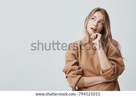 Portrait of pensive fair-haired dreamy hipster girl imagines something in her mind, looks upwards, being deep in thoughts, touching chin. Attractive young blonde female dreams about weekends