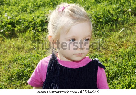 Portrait of pensive girl sitting on the grass
