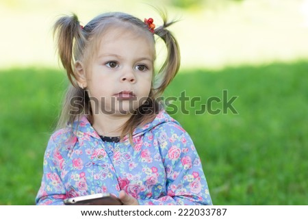 Portrait of pensive girl with pigtails in the park. Two years.