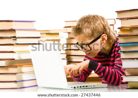 Portrait of pensive lad in eyeglasses typing on laptop between piles of books