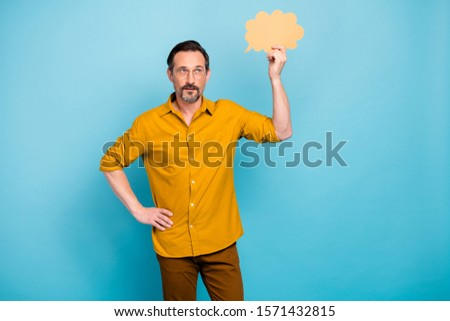 Portrait of pensive man hold yellow speech cloud think thoughts contemplate wear casual style pants trousers isolated over blue color background