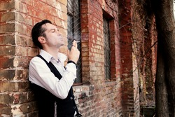 Portrait of pensive man smoking cigarette while leaning on a wall
