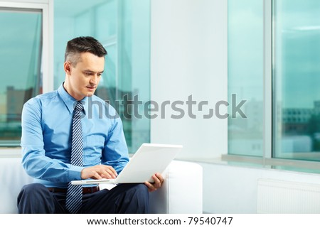 Portrait of pensive man typing in office