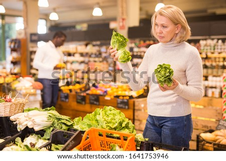 Portrait of pensive mature woman buying fresh organic vegetables in supermarket
