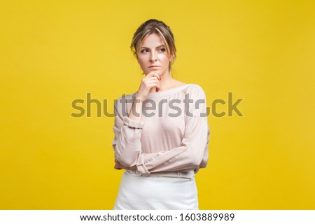 Portrait of pensive or confused young woman with blonde hair in casual beige blouse standing, holding her chin and thinking over problem solution. indoor studio shot isolated on yellow background