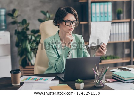 Portrait of pensive planing girl broker lawyer representative chief hold aim progress startup presentation statistics read look analyze sit desk chair in workstation Zdjęcia stock ©