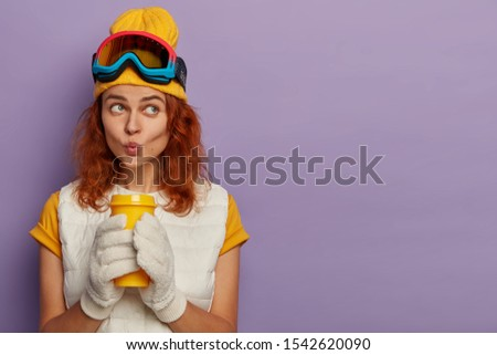 Portrait of pensive redhead woman dressed in casual wear, keeps lips rounded, enjoys aromatic beverage gets ready for skiing wears protective glasses on head poses indoor. Extreme sport, winter season