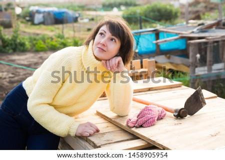 Portrait of pensive woman having break resting during work in garden