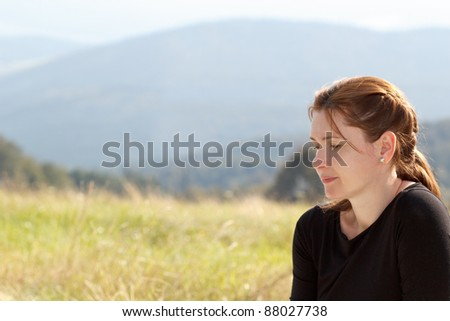 Portrait of pensive woman on mountains background