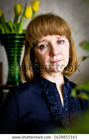 Portrait of pensive woman standing indoors looking into camera. Vase with tulips on the background. Daylight illumination from the window.