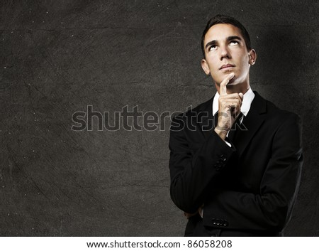 portrait of pensive young business man against a grunge background