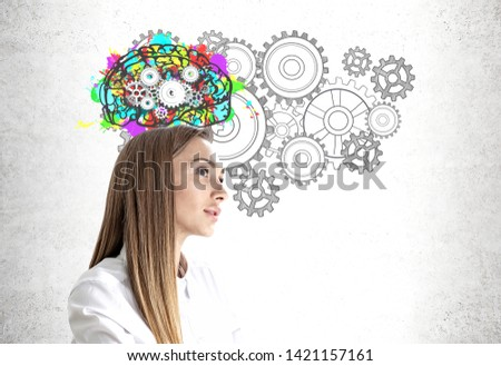 Portrait of pensive young businesswoman with long hair wearing white shirt standing near concrete wall with colorful brain with gears drawn on it. Concept of brainstorming