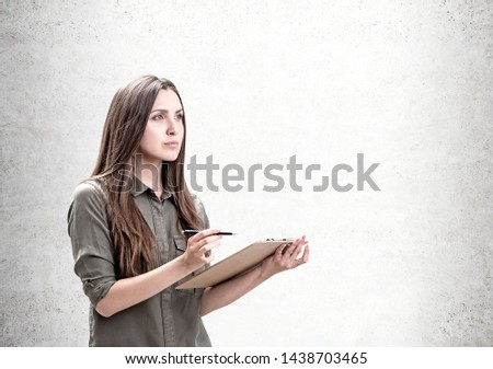 Portrait of pensive young caucasian woman with long fair hair wearing khaki shirt and making notes in clipboard standing near concrete wall. Concept of planning and design. Mock up