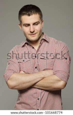 Portrait of pensive young handsome guy over gray background