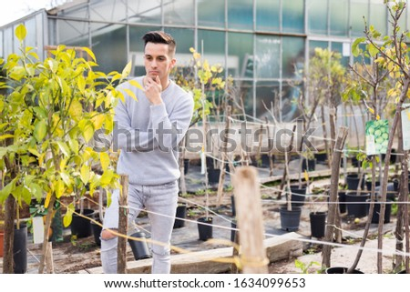 Portrait of pensive young man choosing plants for his garden in greenhouse