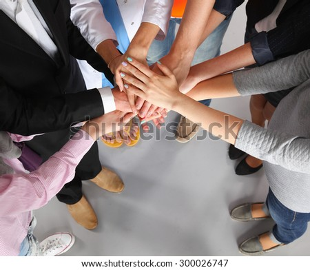 Portrait of people with various occupations putting their hands on top of each other