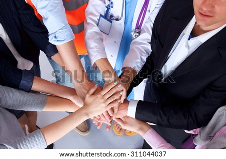 Portrait of people with various occupations putting their hands on top of each other Stock photo ©