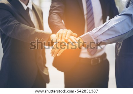 Portrait of people with various occupations putting their hands on top of each other,Stack of hands - real people agreement,Hands of business people on top of each other. Symbolic picture.