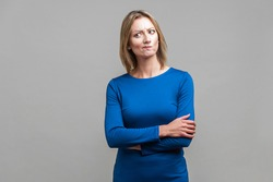 Portrait of perplexed thoughtful woman in tight blue dress standing with hands on her belly, looking aside with doubting inquiring expression. indoor studio shot isolated on gray background