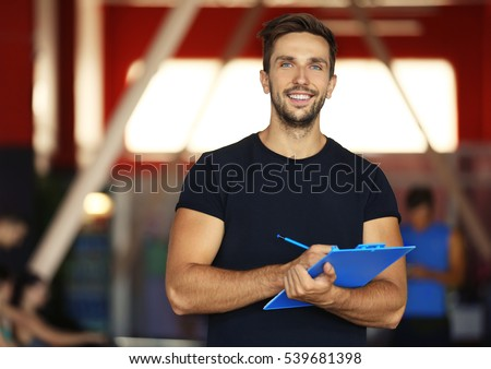 Portrait of personal trainer holding clipboard with training plan in gym Stock fotó ©