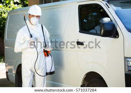 Portrait of pest control man standing next to a van on a street #571037284