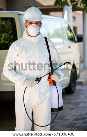 Portrait of pest control man standing next to a van on a street #571038430